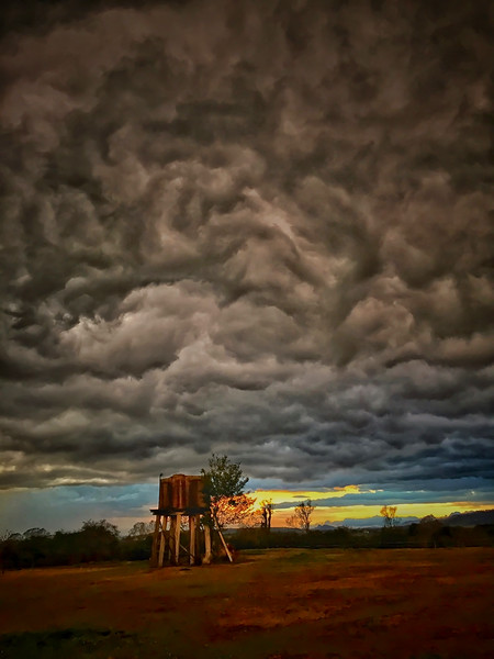 Crazy clouds and the old header tank.jpeg