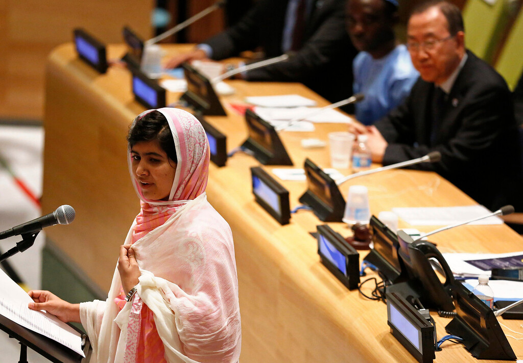 . Malala Yousafzai (L) gives her first speech since the Taliban in Pakistan tried to kill her for advocating education for girls, at the United Nations Headquarters in New York, July 12, 2013. Wearing a pink head scarf, Yousafzai told U.N. Secretary-General Ban Ki-moon (top R) and nearly 1,000 students from around the world attending a Youth Assembly at U.N. headquarters in New York that education was the only way to improve lives. REUTERS/Brendan McDermid