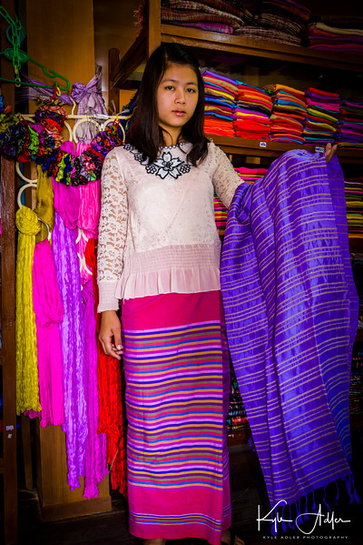 An employee at the fabric workshop shows us garments woven from a mix of lotus plant fiber and silk.