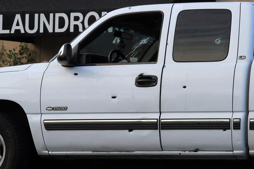 . Oakland police investigate a white truck with multiple bullets holes believed to be involved in a shooting of a Hayward police officer that was found on Edes and 98th Avenues in Oakland, Calif., on Wednesday, July 22, 2015. (Laura A. Oda/Bay Area News Group)