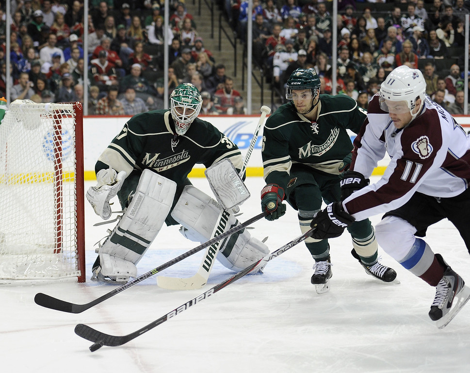 . Jamie McGinn #11 of the Colorado Avalanche controls the puck against Marco Scandella #6 of the Minnesota Wild after a rebound off Josh Harding #37 of the Minnesota Wild during the first period of the game on November 29, 2013 at Xcel Energy Center in St Paul, Minnesota. (Photo by Hannah Foslien/Getty Images)