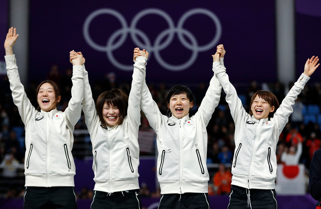 . Gold medalist team Japan with Ayaka Kikuchi, Ayano Sato, Miho Takagi, and Nana Takagi, from left to right center, left, celebrates on the podium after after the women\'s team pursuit final speedskating race at the Gangneung Oval at the 2018 Winter Olympics in Gangneung, South Korea, Wednesday, Feb. 21, 2018. (AP Photo/John Locher)