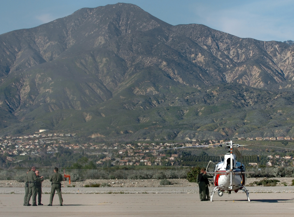 . San Bernardino County Sheriff stand ready by their helicopter at Redlands Airport as police move in on Christopher Dorner in the Big Bear area February 12, 2013.  (Thomas R. Cordova/Staff Photographer)