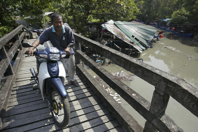 . A man pushes his motorcycle over a bridge in the fishing village of Balik Pulau, Penang, 27 December 2004. The fishing village was the hardest-hit area in Penang. A tsunami hit the northwestern region of Peninsular Malaysia and other countries yesterday after an earthquake measuring 8.9 on the Richter scale occurred off the coast of Sumatra, Indonesia. The earthquake and ensuing tsunami and aftershocks have claimed over 14,000 lives in the south and southeast region of Asia. TENGKU BAHAR/AFP/Getty Images