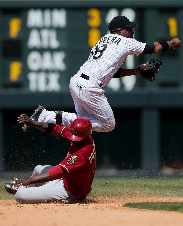 . Shortstop Jonathan Herrera #18 of the Colorado Rockies gets upended by a sliding Didi Gregorius #1 of the Arizona Diamondbacks on a double play attempt during the fifth inning at Coors Field on May 22, 2013 in Denver, Colorado. The Rockies defeated the Diamondbacks 4-1.  (Photo by Justin Edmonds/Getty Images)