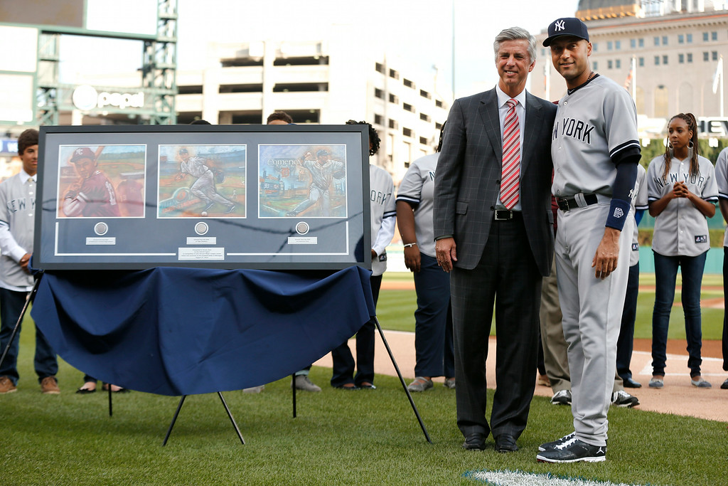 . Detroit Tigers general manager Dave Dombrowski stands with New York Yankees shortstop Derek Jeter in a special on-field ceremony before a baseball game in Detroit Wednesday, Aug. 27, 2014. (AP Photo/Paul Sancya)