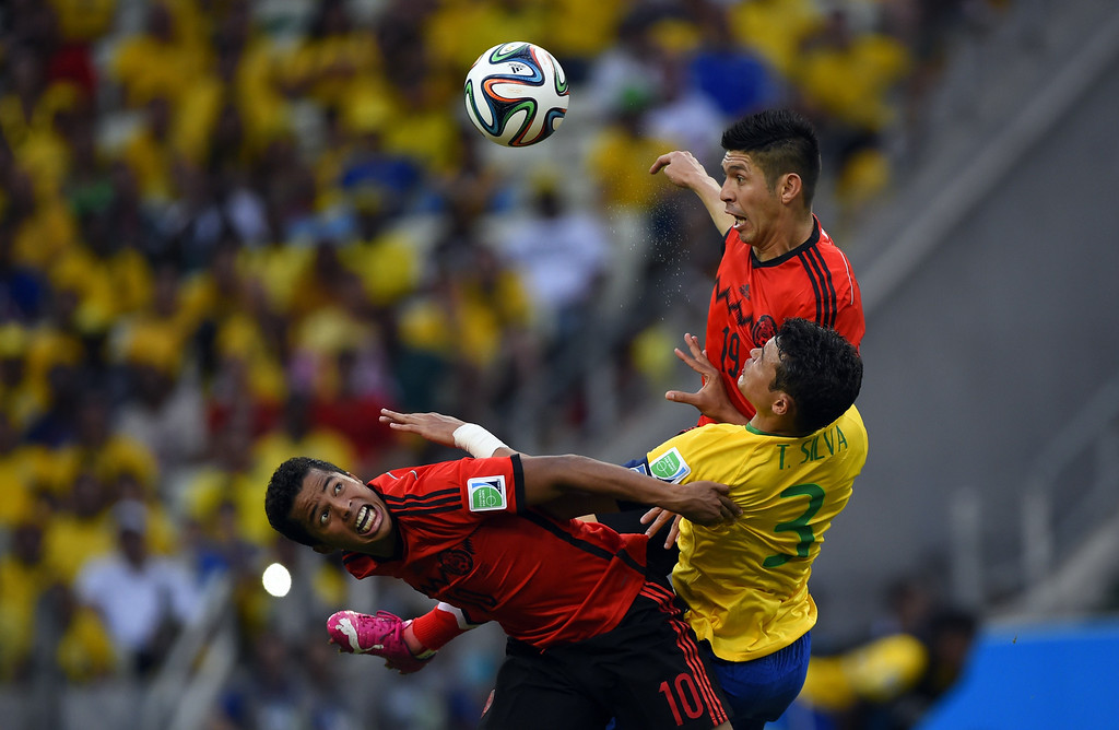 . Mexico\'s forward Giovani Dos Santos (L) and Mexico\'s forward Oribe Peralta (R) vie with Brazil\'s defender Thiago Silva during a Group A football match between Brazil and Mexico in the Castelao Stadium in Fortaleza during the 2014 FIFA World Cup on June 17, 2014. ODD ANDERSEN/AFP/Getty Images