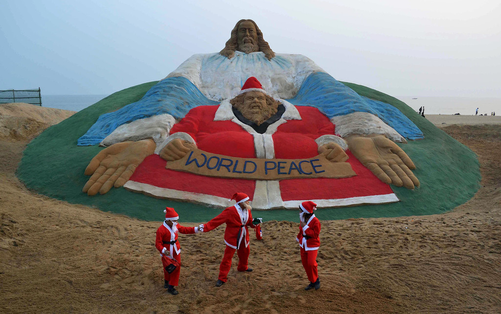 . Indian children dressed as Santa Claus play near a sand sculpture depicting God and Jesus Christ, and created by sand artist Sudarsan Pattnaik, at Golden Sea Beach in Puri, some 65 kms away from Bhubaneswar on December 24, 2013. Despite Christians forming a little over 2 percent of the billion plus population in India, with Hindus comprising the majority, Christmas is celebrated with much fanfare and zeal throughout the country.  ASIT KUMAR/AFP/Getty Images