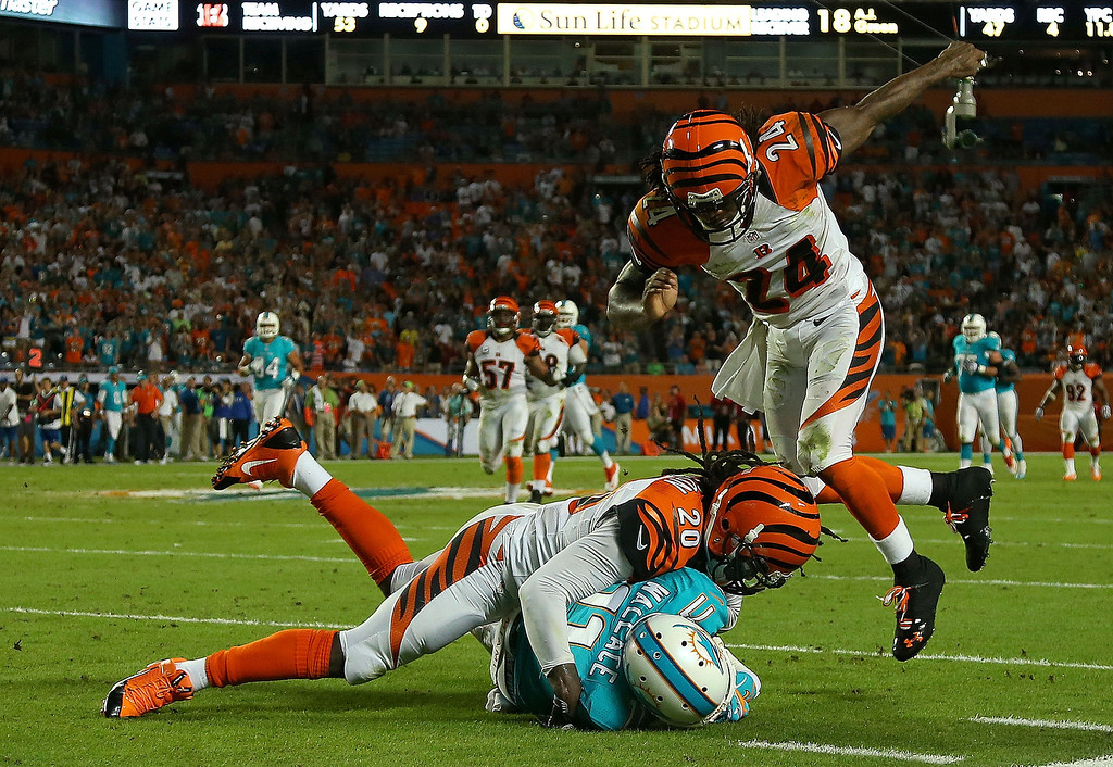 . MIAMI GARDENS, FL - OCTOBER 31: Mike Wallace #11 of the Miami Dolphins is tackled by Reggie Nelson #20 and Adam Jones #24 of the Cincinnati Bengals during a game  at Sun Life Stadium on October 31, 2013 in Miami Gardens, Florida.  (Photo by Mike Ehrmann/Getty Images)