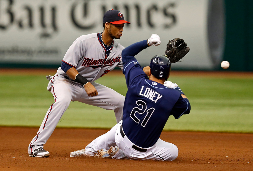 . Tampa Bay\'s James Loney slides in safely with a double as Twins shortstop Pedro Florimon waits for a late throw during the sixth inning. (AP Photo/Mike Carlson)