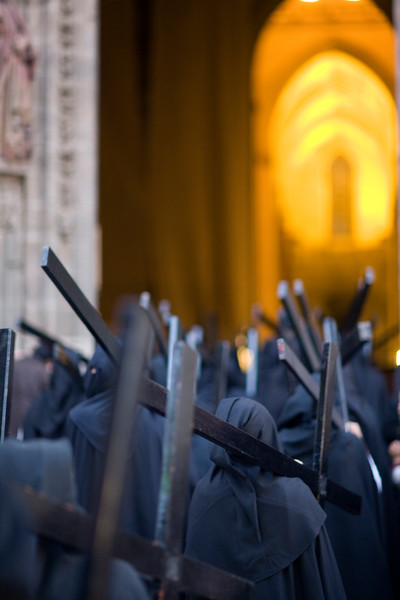 Hooded penitents bearing wooden crosses enter Seville's cathedral, Holy Week 2008, Spain