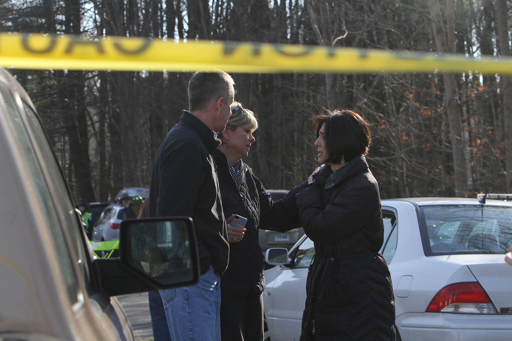 . Teachers walk away from the Sandy Hook School following a shooting at the school Friday, Dec. 14, 2012 in Newtown, Conn. A man opened fire inside the Connecticut elementary school where his mother worked Friday, killing 26 people, including 18 children, and forcing students to cower in classrooms and then flee with the help of teachers and police. (AP Photo/The Journal News, Frank Becerra Jr.)