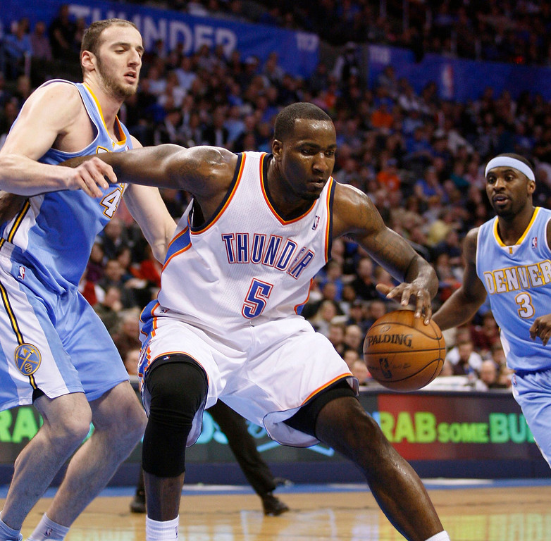. Oklahoma City Thunder center Kendrick Perkins (C) drives against Denver Nuggets defenders Kosta Koufos (L) and Ty Lawson (R) in the second half of their NBA basketball game in Oklahoma City, Oklahoma January 16, 2013. REUTERS/Bill Waugh