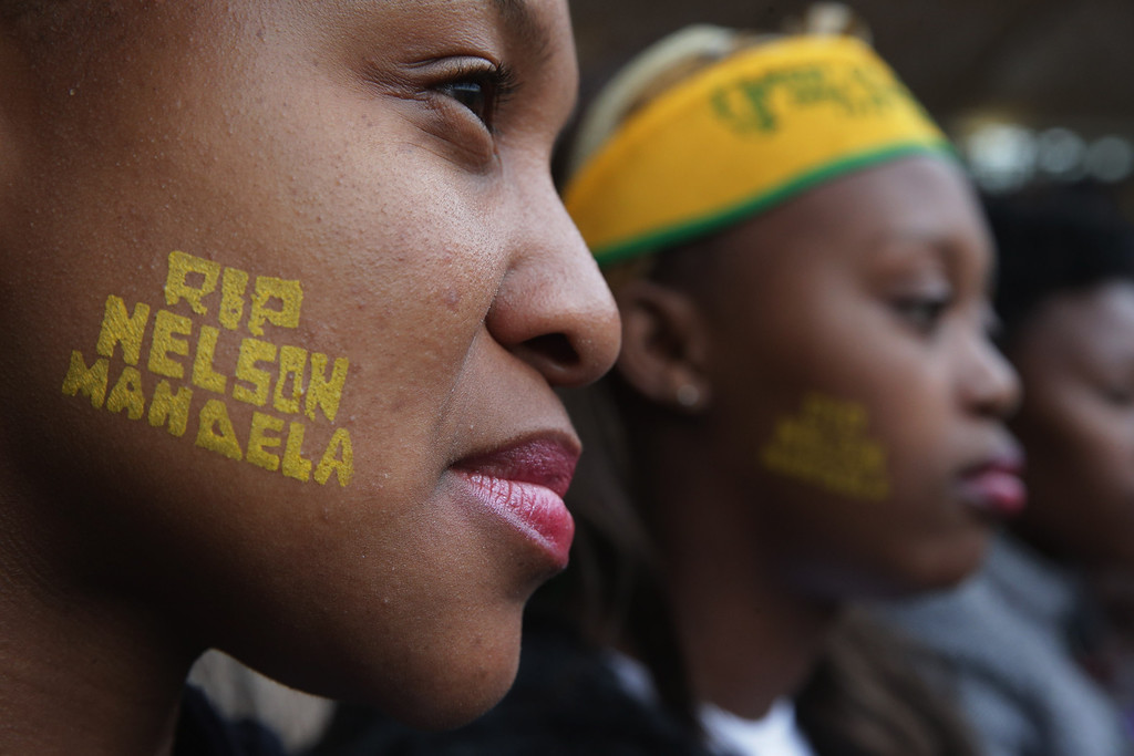 . JOHANNESBURG, SOUTH AFRICA - DECEMBER 10:  Two young women attend the official memorial service for former South African President Nelson Mandela at FNB Stadium December 10, 2013 in Johannesburg, South Africa. Over 60 heads of state have travelled to South Africa to attend a week of events commemorating the life of former South African President Nelson Mandela. Mr Mandela passed away on the evening of December 5, 2013 at his home in Houghton at the age of 95. Mandela became South Africa\'s first black president in 1994 after spending 27 years in jail for his activism against apartheid in a racially-divided South Africa.  (Photo by Chip Somodevilla/Getty Images)