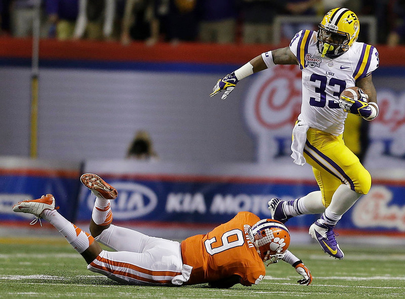 . LSU running back Jeremy Hill (33) runs past Clemson defensive back Xavier Brewer (9) during the first half of the Chick-fil-A Bowl NCAA college football game, Monday, Dec. 31, 2012, in Atlanta. (AP Photo/David Goldman)