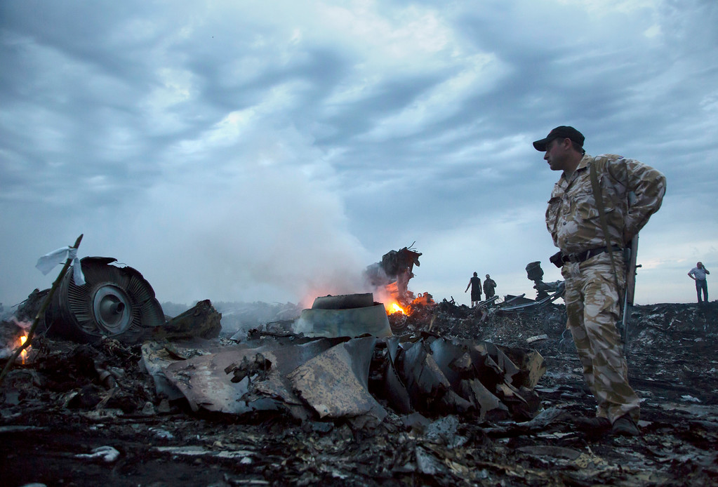 . People walk amongst the debris, at the crash site of a passenger plane near the village of Grabovo, Ukraine, Thursday, July 17, 2014.  A Ukrainian official said a passenger plane carrying 295 people was shot down Thursday as it flew over the country and plumes of black smoke rose up near a rebel-held village in eastern Ukraine. Malaysia Airlines tweeted that it lost contact with one of its flights as it was traveling from Amsterdam to Kuala Lumpur over Ukrainian airspace.  (AP Photo/Dmitry Lovetsky)