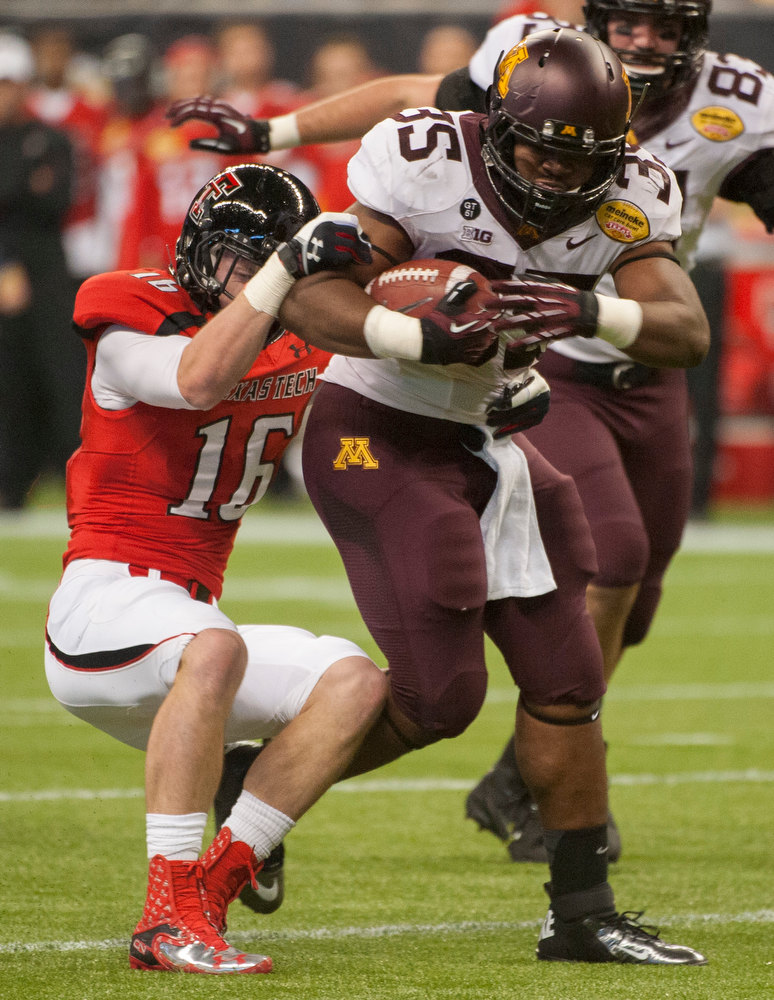 . Minnesota\'s Rodrick Williams (35) runs past Texas Tech\'s Cody Davis (16) during the first quarter of the Meineke Car Care Bowl NCAA college football game, Friday, Dec. 28, 2012, in Houston. (AP Photo/Dave Einsel)