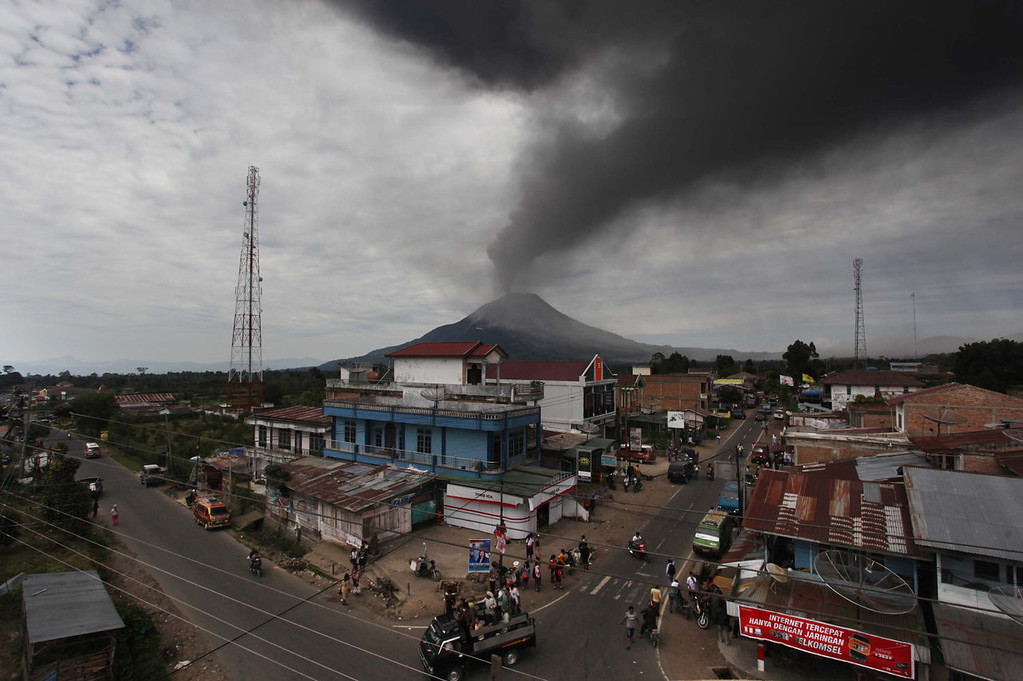 . A cloud of ash rises from the crater of the Mount Sinabung volcano (back C) during a fresh eruption on September 17, 2013, as seen from Karo district. Thousands of villagers fled after Mount Sinabung\'s series of volcanic eruptions on Indonesia\'s Sumatra island, spewing rocks and red-hot ash onto surrounding villages, officials said.   ADE SINUHAJI/AFP/Getty Images