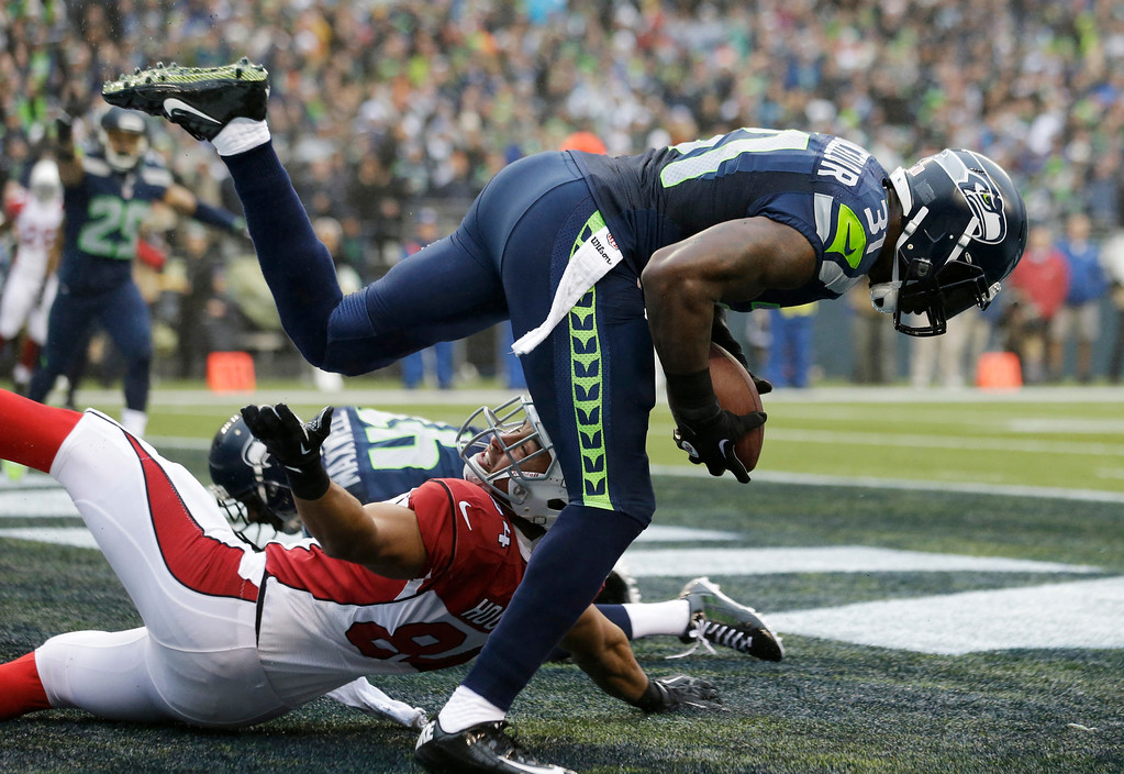 . Seattle Seahawks strong safety Kam Chancellor, right, comes down with an interception of a pass intended for Arizona Cardinals tight end Rob Housler, lower left, in the first half of an NFL football game, Sunday, Dec. 22, 2013, in Seattle. (AP Photo/Elaine Thompson)
