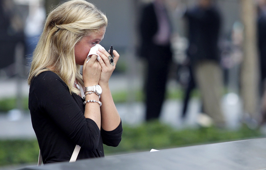 . Kayla Fallon, daughter of William Fallon who perished in Tower One when she was 8 years old, reacts as she attends ceremonies for the twelfth anniversary of the terrorist attacks on lower Manhattan at the World Trade Center site on September 11, 2013 in New York City. (Photo by John Angelillo-Pool/Getty Images)