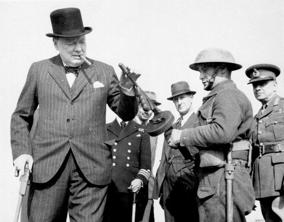 . 1940: Winston Churchill. British Prime Minister Winston Churchill is passed a machine gun during a visit to north east England, August 1, 1940, to inspect coastal fortifications. (AP Photo/British Official Photo)
