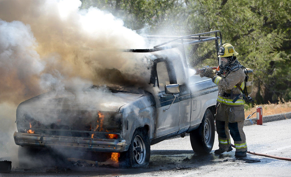 . Ontario firefighter Danny Reza gets water on a vehicle fire on the Vineyard offramp Thursday May 2, 2013. Marco Perez of Riverside said he smelled gas coming from his truck and pulled over to the shoulder of the Vineyard Avenue offramp of the westbound 10. No one was injured and the cause of the fire is under investigation. (Rick Sforza/Inland Valley Daily Bulletin)