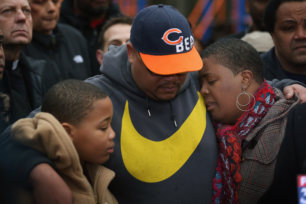 Description of . Nate Pendleton comforts his son Nathaniel, 10, and his wife Cleopatra as they listen to speakers at a press conference in a neighborhood park where Nate's daughter Hadiya was killed on January 30, 2013 in Chicago, Illinois. Fifteen-year-old Hadiya was shot and killed when a gunman opened fire in the park yesterday while she was hanging out with friends on the warm rainy afternoon under a shelter in the park. Hadiya was a majorette in her high school band and recently performed in Washington, D.C. during the inauguration. President Obama's Chicago home is less than a mile from the park where Hadiya was killed.   Another person was wounded in the leg during the shooting.   (Photo by Scott Olson/Getty Images)