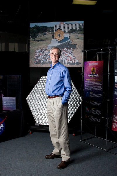 Dr. John Mather, Nobel Laureate in Physics 2006, Senior Project Scientist, James Webb Space Telescope, NASA/Goddard Space Flight Center stands in front of a full-size model of part of JWST and a photo of a full-size mockup of the entire spacecraft.