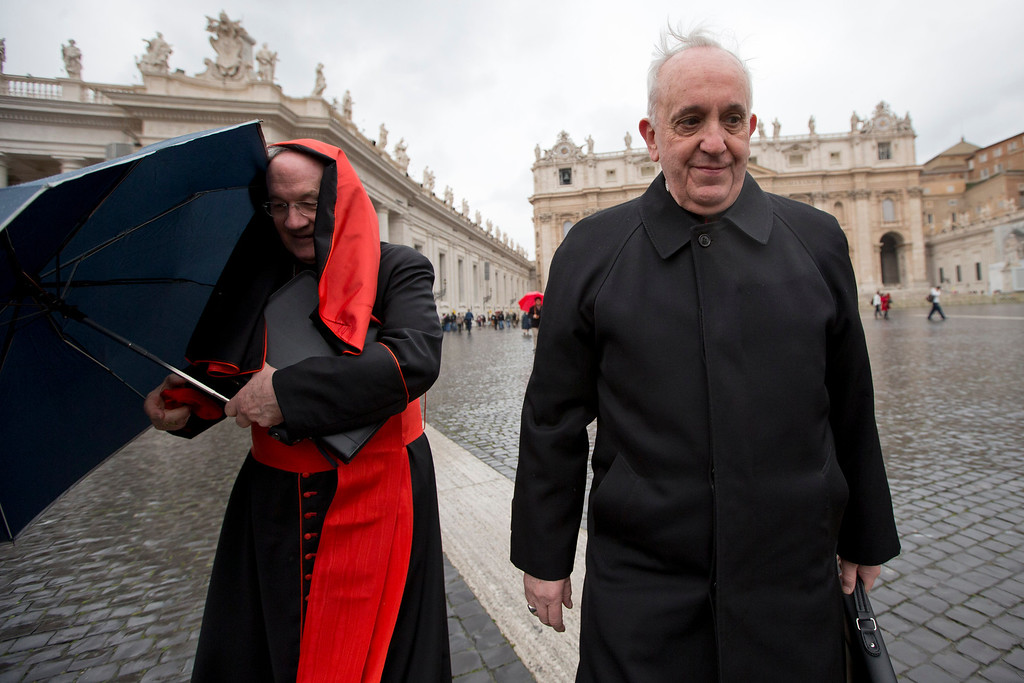 . Canadian Cardinal Marc Ouellet, left, holds on to his umbrella next to Argentine Cardinal Jorge Mario Bergoglio as they walk in St. Peter\'s Square after attending a cardinals\' meeting, at the Vatican, Wednesday, March 6, 2013. Cardinals are meeting to discuss the problems of the church and to get to know one another because there is no clear front-runner in the election of the new pope. (AP Photo/Andrew Medichini)