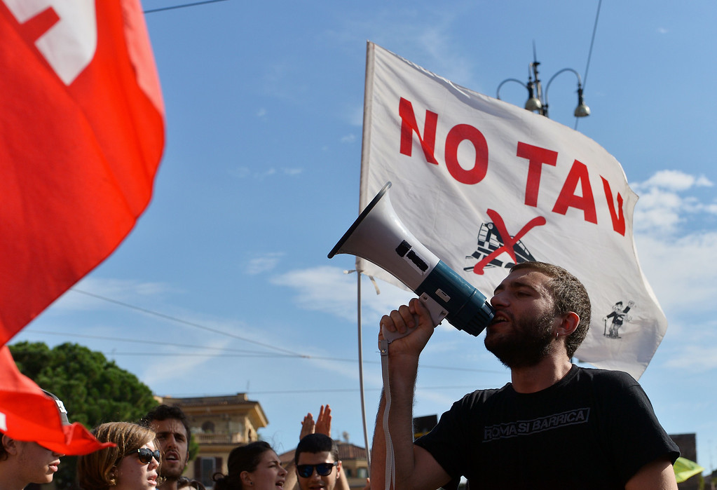 . A man uses a horn speaker during an anti-austerity protest led by anti high-speed rail movement (No Tav) and an association for rights to housing, on October 19, 2013 in Rome. Between 3,000 and 4,000 police officers have been deployed, Italian media reports said, and protest organizers say they expect more than 20,000 to join.  ALBERTO PIZZOLI/AFP/Getty Images