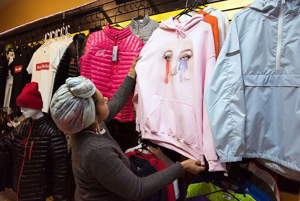11/21/18 Wesley Bunnell | Staff Adrianna Martinez, sales manager for The Hive, hangs a sweatshirt by local company Sappho Clothing for sale in anticipation of the upcoming kickoff to holiday sales on Wednesday afternoon.