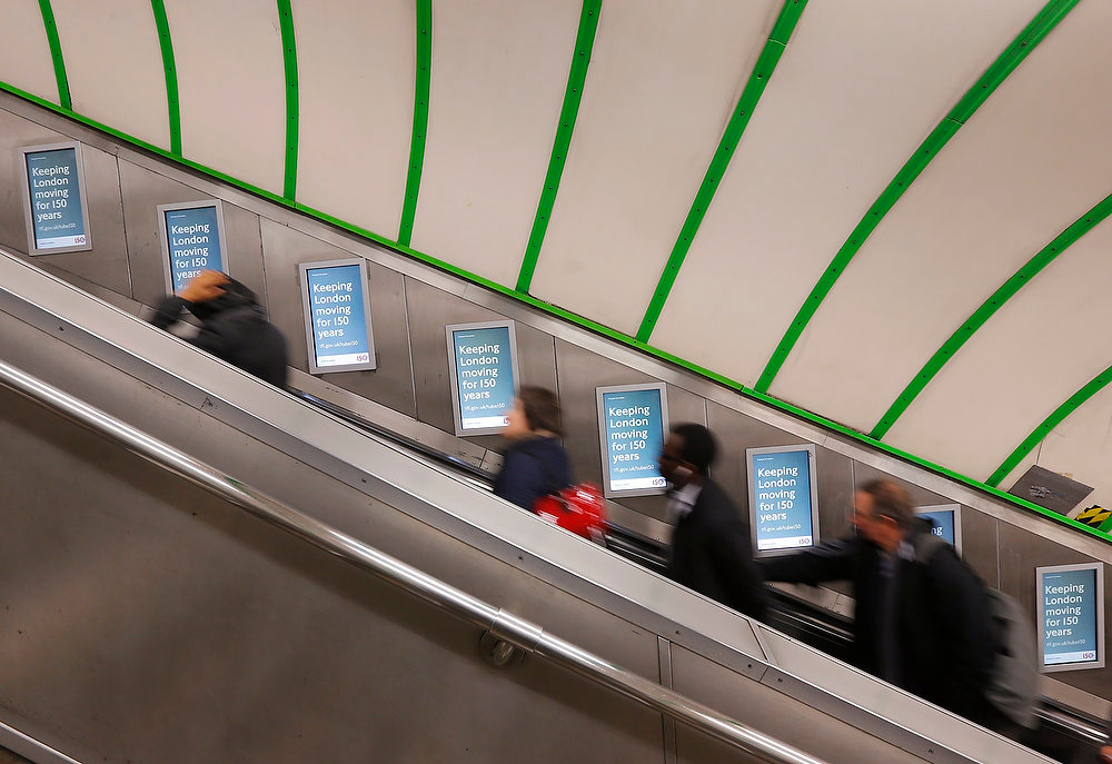 Description of . Passengers use the escalator at Paddington Underground station, passing posters highlighting London Underground's 150th anniversary, in London on January 9, 2013. London Underground celebrates 150 years since the first underground journey took place between Paddington and Farringdon on January 9, 1863.  REUTERS/Andrew Winning