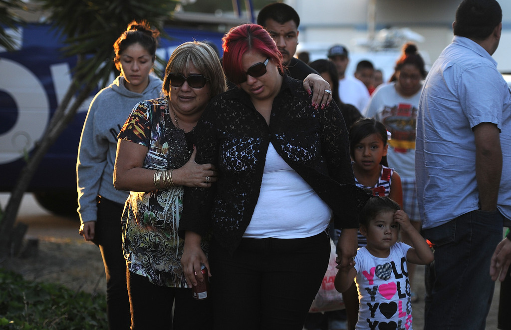 . Myra Velasquez, center, wife of Efren Velasquez is consoled by friends and family as she makes her way to a make shift memorial for those who died in a car crash including two children and a man along the 3500 block of San Gabriel River Road on Friday, June 14, 2013 in Industry, Calif.  (Keith Birmingham/Pasadena Star-News)