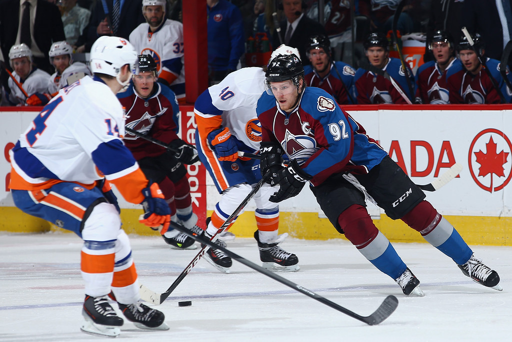 . DENVER, CO - JANUARY 10:  Gabriel Landeskog #92 of the Colorado Avalanche controls the puck against Thomas Hickey #14 of the New York Islanders at Pepsi Center on January 10, 2014 in Denver, Colorado.  (Photo by Doug Pensinger/Getty Images)