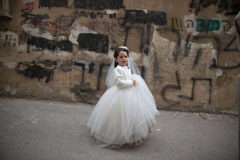 . An Ultra-Orthodox Jewish girl dressed in costume walks in the street during the Purim holiday in the ultra-orthodox Mea Shearim neighborhood in Jerusalem on March 17, 2014. The carnival-like Purim holiday is celebrated with parades and costume parties and drinking wine to commemorate the deliverance of the Jewish people from a plot to exterminate them in the ancient Persian empire 2,500 years ago, as recorded in the Biblical Book of Esther. (MENAHEM KAHANA/AFP/Getty Images)