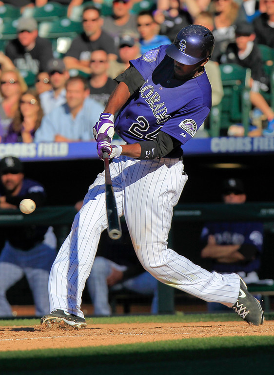 . Colorado Rockies\' Dexter Fowler (24) hits an RBI-single to score Yorvit Torrealba (8) during the bottom of the 10th inning of a baseball game against the Los Angeles Dodgers, Saturday June 1, 2013, in Denver. The Rockies won 7-6. (AP Photo/Barry Gutierrez)
