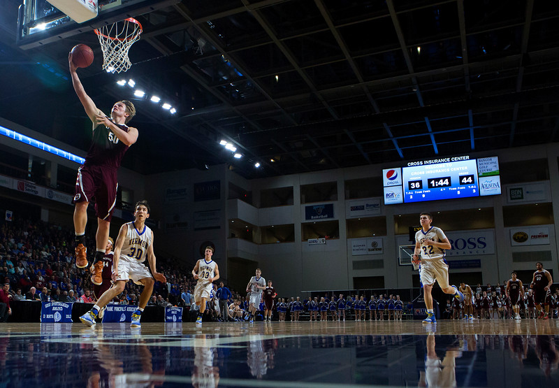 BANGOR, Maine -- 02/22/2017 -- Orono's Keenan Collett (left) sails in a shot past Hermon's Isaac Varney during their Class B boys basketball semifinal game at the Cross Insurance Center in Bangor Wednesday. Ashley L. Conti | BDN