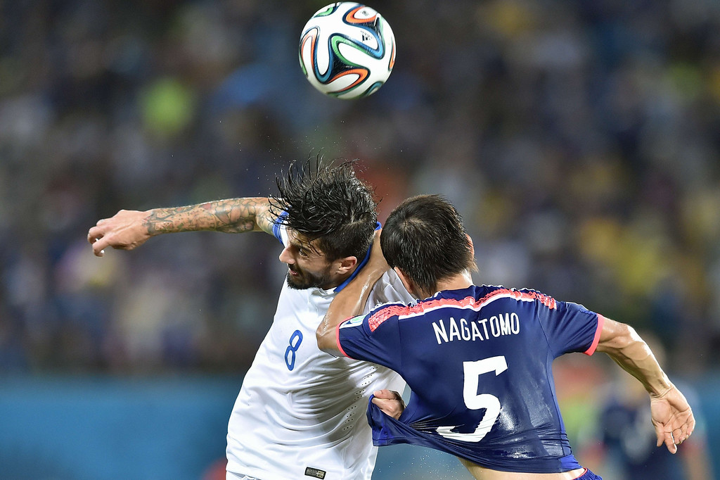 . Greece\'s midfielder Panagiotis Kone (L) in action against Japan\'s defender Yuto Nagatomo during a Group C match between Japan and Greece at the Dunas Arena in Natal during the 2014 FIFA World Cup on June 19, 2014. ARIS MESSINIS/AFP/Getty Images