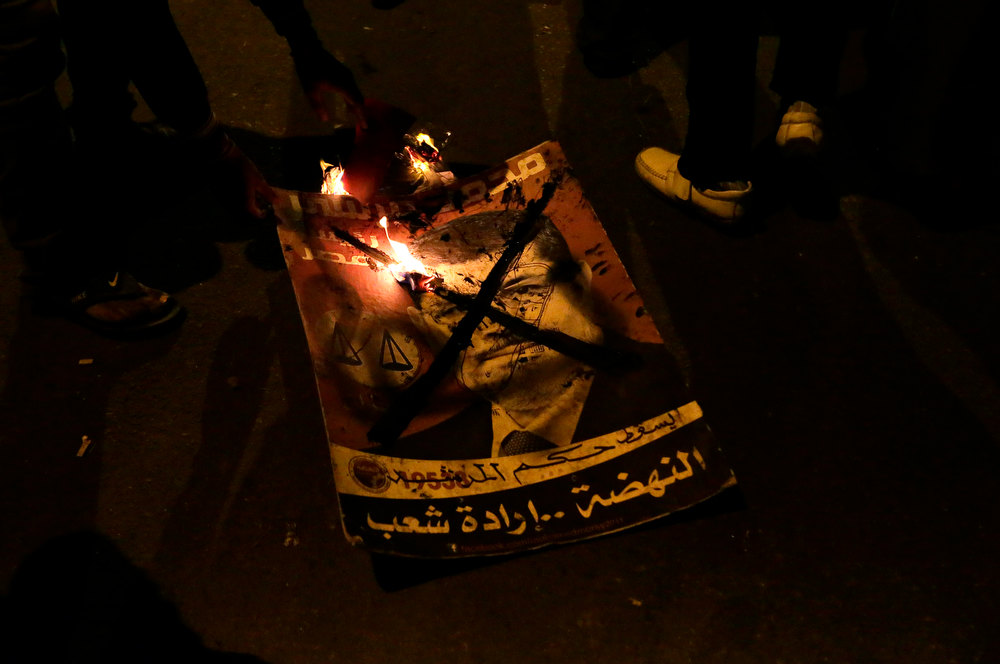". Egyptian protesters burn a picture portraying Egyptian President Mohammed Morsi as they gather outside the presidential palace after they broke a barbed wire barricade that was keeping them from getting closer to the presidential palace, in Cairo, Egypt, Friday, Dec. 7, 2012. Egypt\'s political crisis spiraled deeper into bitterness and recrimination Friday as thousands of Islamist backers of the president vowed vengeance at a funeral for men killed in bloody clashes earlier this week and large crowds of the president\'s opponents marched on his palace to increase pressure after he rejected their demands. Arabic on the poster reads, ""down with the rule of the supreme guide.\"" (AP Photo / Hassan Ammar)"