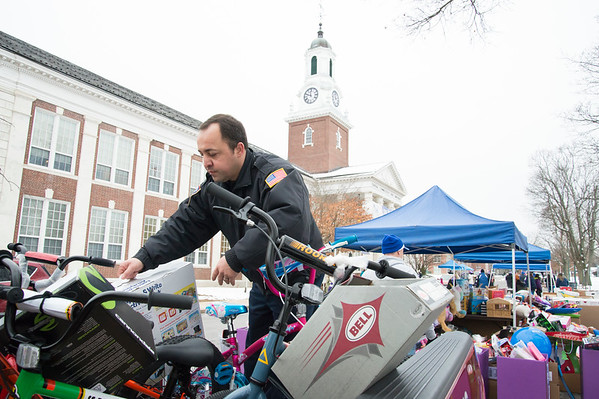 12/13/19 Wesley Bunnell | StaffrrToys, warm clothes, non perishable food items were collected on Friday from 6 a.m. until noon outside of CCSU's Davidson Hall in conjunction with CCSU and The Anna Grace Project's Love Wins. NBFD's Marco Costa loads bicycles and toys onto a fire department pick up truck.