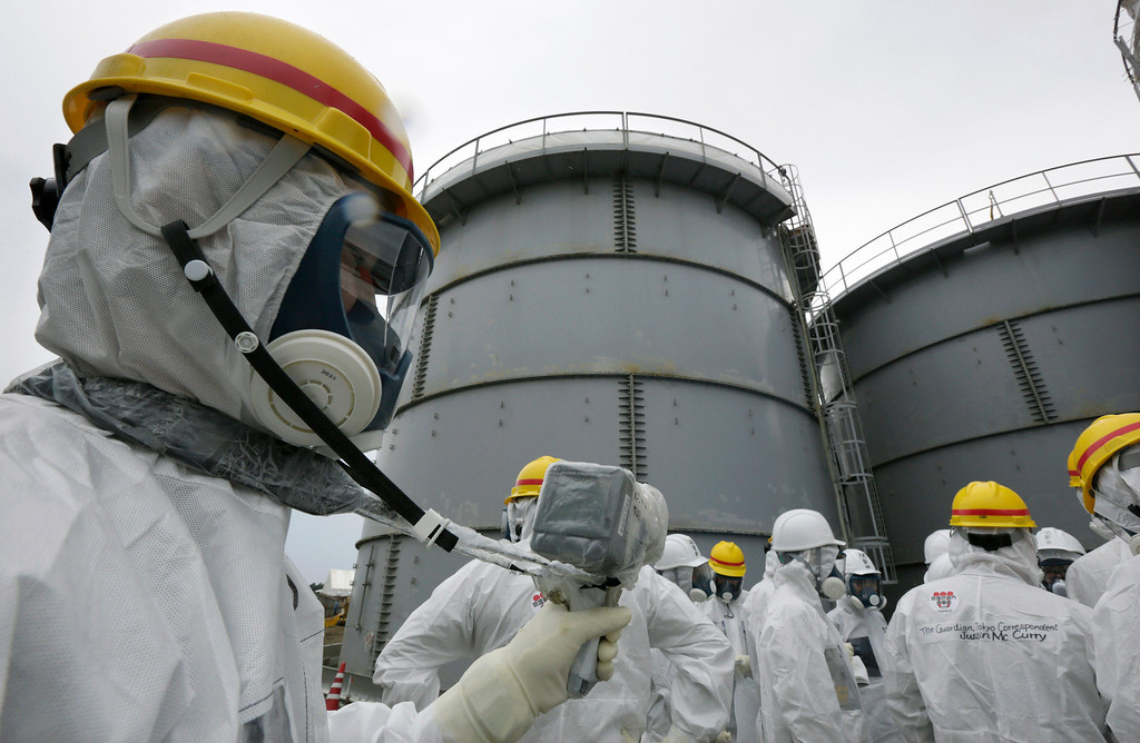 . An official of the Tokyo Electric Power Co. measures radiation at H4 tank area where radioactive water leaked from a storage tank in August, at the Fukushima Dai-ichi nuclear power plant in Okuma, Fukushima Prefecture, Japan, Thursday, Nov. 7, 2013. (AP Photo/Kimimasa Mayama, Pool)