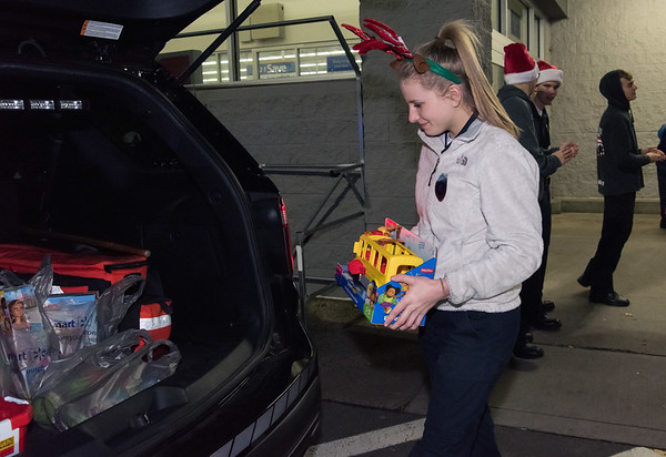 12/03/18 Wesley Bunnell | Staff The Bristol Police Explorers held their annual toy drive outside of Walmart on Monday evening. Police Explorer Katie Bardeck, a Bristol Eastern High School student, places toys in back of the police cruiser.