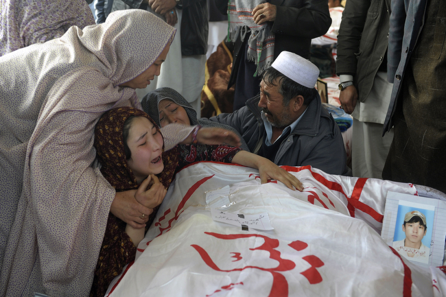 . A Pakistani woman is comforted by other relatives while grieving over the body of her brother Mohammed Ali, who was killed in Saturday\'s bombing, in Quetta, Pakistan, Tuesday, Feb. 19, 2013. Pakistan on Tuesday ordered an operation in the southwestern city of Quetta following a weekend bombing targeting minority Shiite Muslims that killed scores of people there, and sacked the top police officer in the surrounding Baluchistan province as victims of the bombing refuse to bury their dead in protest. (AP Photo/Arshad Butt)