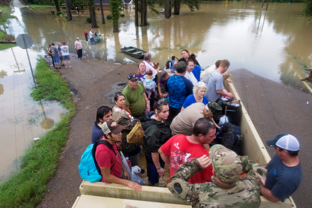 . Sgt. Brad Stone of the Louisiana Army National Guard gives safety instructions to people loaded on a truck after they were stranded by rising floodwater near Walker, La., after heavy rains inundated the region, Sunday, Aug. 14, 2016. (AP Photo/Max Becherer)