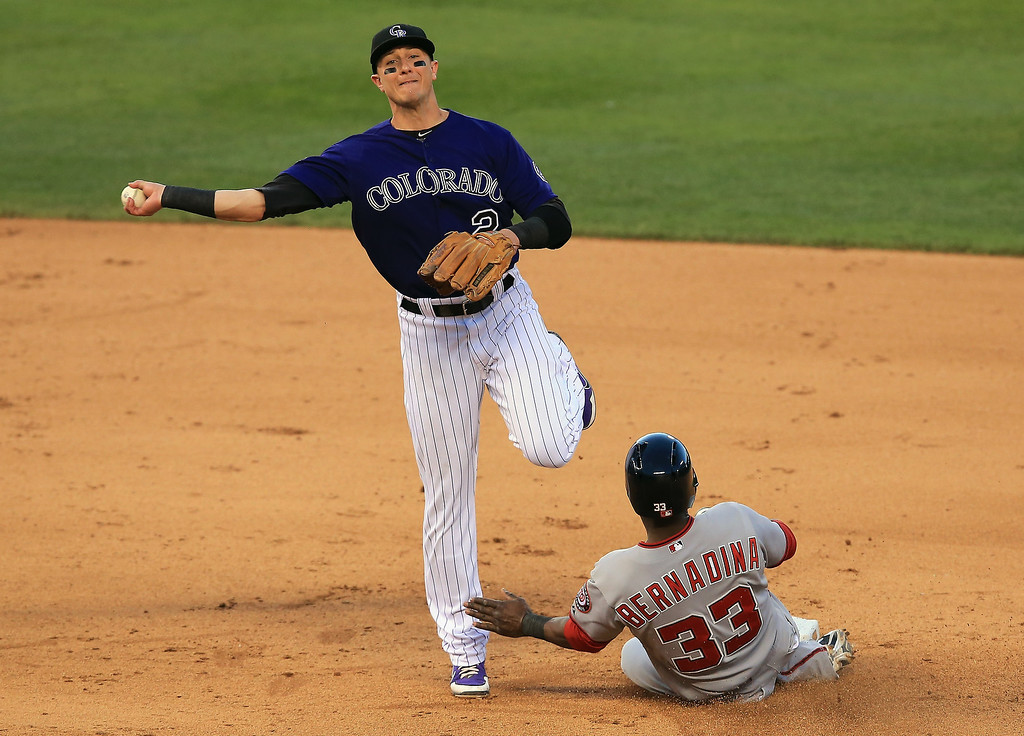 . Shortstop Troy Tulowitzki #2 of the Colorado Rockies turns a double play on Roger Bernadina #33 of the Washington Nationals on a ball hit by Ryan Zimmerman #11 of the Washington Nationals in the fifth inning at Coors Field on June 11, 2013 in Denver, Colorado.  (Photo by Doug Pensinger/Getty Images)