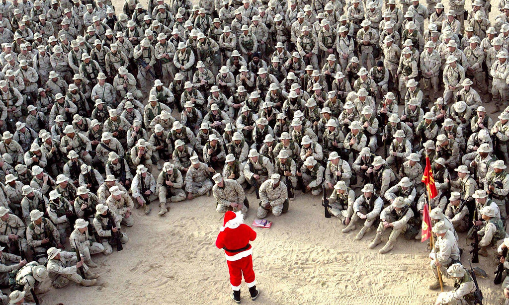 . In this Tuesday, Dec. 24, 2002 file photo made by Associated Press photographer Anja Niedringhaus, hundreds of U.S. Marines gather at Camp Commando in the Kuwait desert during a Christmas eve visit by Santa Claus. (AP Photo/Anja Niedringhaus, File)