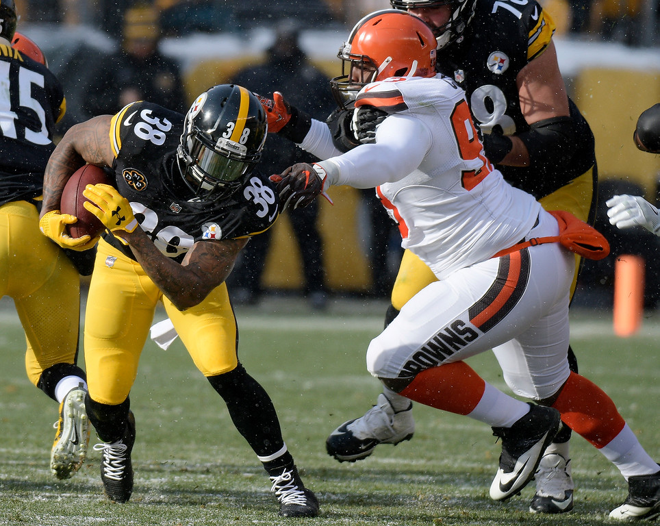 . Pittsburgh Steelers running back Stevan Ridley (38) slips past Cleveland Browns defensive tackle Trevon Coley (93) during the first half of an NFL football game in Pittsburgh, Sunday, Dec. 31, 2017. (AP Photo/Don Wright)