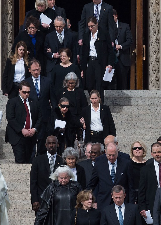 . US Supreme Court Chief Justice John Roberts (bottom R) and justices Anthony Kennedy (2nd row R), Clarence Thomas (2nd row C), Ruth Bader Ginsburg (C, with sunglasses), Samuel Alito (center row L), Elena Kagan (center row C), Sonia Soto-mayor (top L) and retired justice David Souter (with Sotomayor) walk out of the Basilica of the National Shrine of the Immaculate Conception after the funeral mass for Justice Antonin Scalia on February 20, 2016 in Washington, DC. Scalia died on February 13 at the age of 79. / AFP / Nicholas Kamm / The erroneous mention appearing in the metadata of this photo by Nicholas Kamm has been modified in AFP systems in the following manner: [Ruth Bader Ginsburg] instead of [Ruth Bader Ginzburg]. Please immediately remove the erroneous mention from all your online services and delete it from your servers. If you have been authorized by AFP to distribute it to third parties, please ensure that the same actions are carried out by them. Failure to promptly comply with these instructions will entail liability on your part for any continued or post notification usage. Therefore we thank you very much for all your attention and prompt action. We are sorry for the inconvenience this notification may cause and remain at your disposal for any further information you may require.NICHOLAS KAMM/AFP/Getty Images