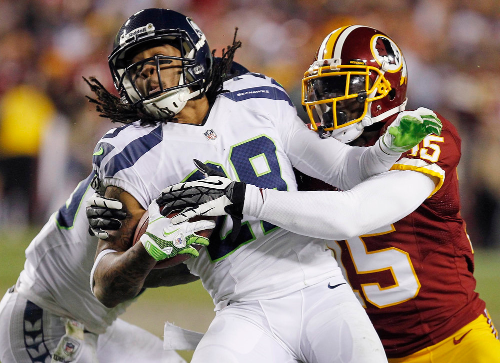 . Seattle Seahawks free safety Earl Thomas (29) is tackled by Washington Redskins wide receiver Josh Morgan (15) after intercepting a pass in the first half during their NFL NFC wildcard playoff football game in Landover, Maryland, January 6, 2013. REUTERS/Tim Shaffer
