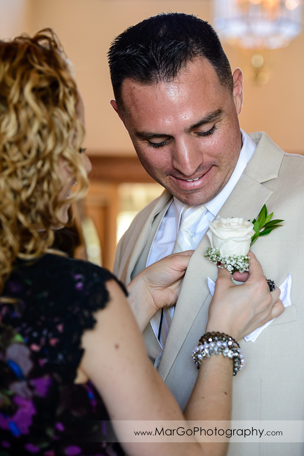women putting on groom's buttonhole